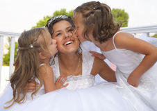 Wedding day. Flower-girls kiss the bride outside Stock Images