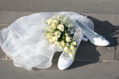 Wedding day. The wedding white shoes, bouquet and easy addition are on ground Royalty Free Stock Photos