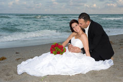 Wedding day. Handsome groom kissing beautiful bride at the beach Royalty Free Stock Photo
