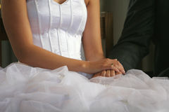 Wedding day. A wedding, bride and groom sitting holding hands after ring ceremony, cropped shot of hands Royalty Free Stock Photography