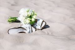 Wedding day. Bridal bouquet and sandals lie on the sand Stock Photos