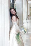 Wedding day bride. Bride in traditional white wedding dress stood with bouquet Stock Image