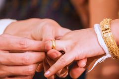 On the wedding day, the bride and groom have to exchange sweet together by pushing the ring together. Stock Photography