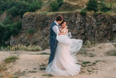 Wedding day. The bride and groom tenderly embrace each other against the backdrop of wildlife at sunset. stock photos