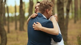 Wedding day. The bride hugs the groom. Loving couple in a pine forest. Looking at each other. Wedding day. The bride hugs the groom. Loving couple in a pine stock video footage