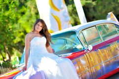 Wedding day. A bride, just married, sitting on a retro car stock photo