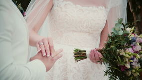 On a wedding day bride puts a golden ring on a groom finger. Close-up exchanging wedding rings. stock video