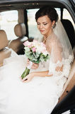 Wedding day. Bride is sitting and smiling in a car with wedding Royalty Free Stock Images