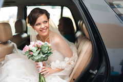 Wedding day. Bride is sitting and smiling in a car with wedding Stock Photo