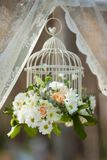 Wedding day flowers. White flowers in cage, wedding decorations on sunny day Royalty Free Stock Images