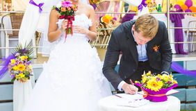 Wedding day - groom make the signature. Happy wedding day - groom make the signature Stock Images