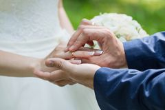 The groom places the ring on the bride& x27;s hand. Photo closeup Royalty Free Stock Images