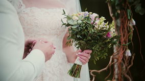 On a wedding day groom puts a golden ring on a bride finger. Close-up exchanging wedding rings stock video