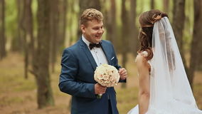 Wedding day. Happy couple and touching. The groom embraces the bride in a pine forest and gives a bouquet. The bride was. Touched stock video footage