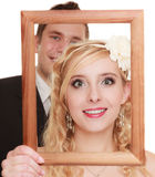 Wedding day. Happy couple in wooden frame isolated Royalty Free Stock Images