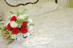 Wedding day. A pair of wedding rings and bridal bouquet of flowers on the bed Royalty Free Stock Image