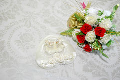 Wedding day. A pair of wedding rings and bridal bouquet of flowers on the bed Stock Photography