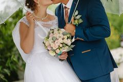 Wedding day. Portrait of a happy married couple with bride and groom with umbrella and bouquet of flowers. Scraped without the face of the newlyweds Stock Photo
