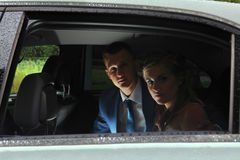 Wedding day in rainy weather, couple sitting in the car. Stock Photography