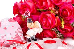 Wedding day. Red roses, bride and fiance, candle and gift box close up picture Royalty Free Stock Photography