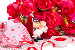 Wedding day. Red roses, bride and fiance, candle and gift box close up picture Stock Photo
