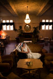 Wedding day relaxation. A bride and groom relaxing on a plush sofa in a sepia-colored, antique style hotel reception room Royalty Free Stock Photography