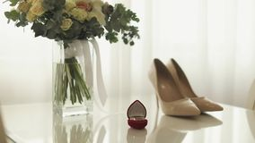 Wedding day. Wedding rings and bride`s bouquet on the table stock footage