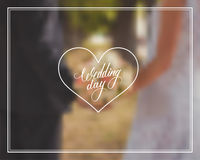 Wedding day typography element on blurred background. Wedding bouquet in brides and grooms hands. Royalty Free Stock Photo