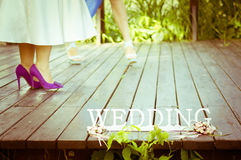 Wedding day. Women's legs on the wood terrace near the lake. Wedding symbol standing in the right corner Royalty Free Stock Photos