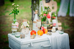 Wedding decor with bottles, glasses, roses, vases and peaches on Stock Images