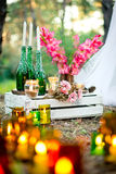 Wedding decor with the burning candles, bottles, gladiolus. Royalty Free Stock Photos