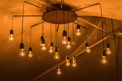 Wedding decor. Glowing light bulbs in an old chandelier in the tent Stock Image