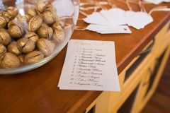 Golden walnut in a glass round vase and a guest seating list. Wedding decor. Wedding decor. Golden walnut in a glass round vase and a guest seating list royalty free stock images
