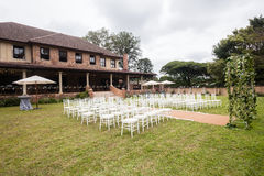 Wedding Decor Home. Wedding decor setup chairs ceremony on grass lawn cutlery glasses table on porch veranda at private home mansion Stock Photography