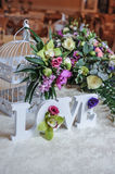 Wedding decor, LOVE letters and flowers on table. Fresh flowers and LOVE decoration on festive table. Luxurious wedding decoration. On restaurant table. Elegant stock image