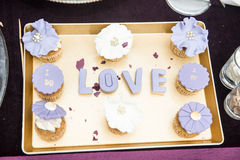 Wedding decor, LOVE letters on tray with blue colored muffins. LOVE decoration on festive table. Luxurious wedding decoration. On restaurant table. Elegant stock image