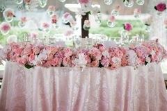 Wedding decor in the restaurant. Festive decor for a wedding in the restaurant. Wedding decor with roses, lights and glasses royalty free stock photography