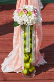 Wedding decor vase with apple and flowers. Wedding ceremonydecor with apple and flowers in coral color Royalty Free Stock Image