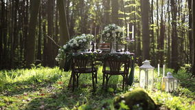 Wedding decorated table setted for two on nature in the forest. Wedding decoration of white roses bouquets and vintage. Candles with lanterns stock footage
