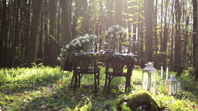 Wedding decorated table setted for two on nature in the forest. Wedding decoration of white roses bouquets and vintage. Candles with lanterns stock video footage