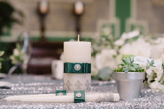 Wedding decorated candles with the silver brooch and green ribbons next to silver pot. Wedding decorated white candles with the silver brooch and green ribbons Stock Photos