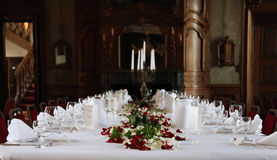 Wedding decoration. Photo shows a nice red rose floral flowering on a wedding decorated table with a glasses for sparkling vine and some small hearts with Royalty Free Stock Photo