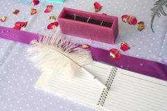 Wedding decoration. Pink notebook and a feather pen on a wedding guest table Royalty Free Stock Images