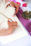 Wedding decoration. Pink notebook and a feather pen on a wedding guest table Stock Image