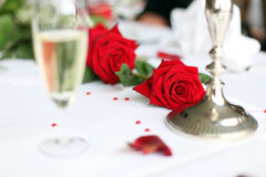 Wedding decoration. Photo shows a nice red rose on a wedding decorated table with a glass of sparkling wine and some small hearts Stock Photo