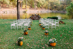 Wedding decoration with autumn pumpkins and flowers. Ceremony outdoor in the park. White chairs for guests Stock Photography