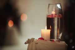 Wedding decoration a candle and a vase with water on a white table. Flasks with water and a floating candle. Wedding decoration a candle and a vase with water on royalty free stock photo