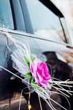 Wedding decoration on car. Rose bridal jewelry to wear on the machine handle Stock Photo