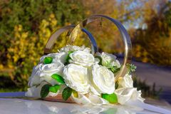 Wedding decoration on the car. Wedding decoration on a car with white roses, golden rings with colokolchiki on the background of the autumn landscape stock photography