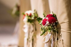 Wedding Decoration on the Chairs. With red and white flowers Stock Images